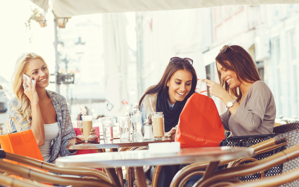 Three young women after shopping at coffee
